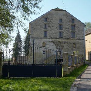 Vue du moulin depuis la rue du Moulin du Loison au travers du grand portail