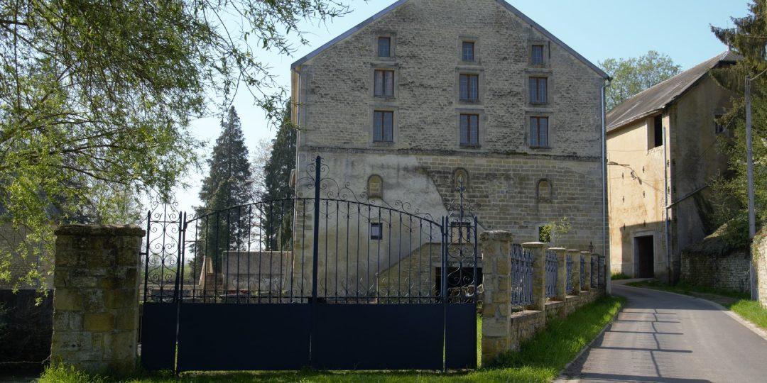 Vue du moulin depuis la rue du moulin au travers du grand portail côté façade avec 3 niches